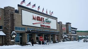 BEMIDJI, MN - 27 DEC 2018: Entrance to Market Place grocery store, Sally, and Office Max during a winter snow storm. BEMIDJI, MN - 27 DEC 2018: Entrance to stock footage