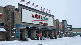 BEMIDJI, MN - 27 DEC 2018: Entrance to Market Place grocery store, Sally, and Office Max during a winter snow storm. BEMIDJI, MN - 27 DEC 2018: Entrance to stock video footage