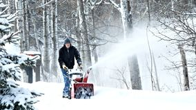 BEMIDJI, MN - 22 JAN 2019: Man works with a snow blower to remove newly fallen snow. BEMIDJI, MN - 22 JAN 2019: Man works with a snow blower to remove newly royalty free stock photography
