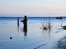 BEMIDJI, MN - 11 MAY 2019: Fisherman wading in Lake Bemidji during opener. BEMIDJI, MN - 11 MAY 2019: Fisherman wading in Lake Bemidji near bridge over the royalty free stock photos