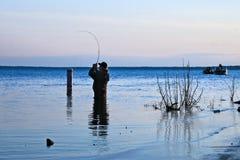 BEMIDJI, MN - 11 MAY 2019: Fisherman wading in Lake Bemidji during opener. BEMIDJI, MN - 11 MAY 2019: Fisherman wading in Lake Bemidji near bridge over the stock photos
