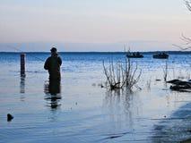 BEMIDJI, MN - 11 MAY 2019: Fisherman wading in Lake Bemidji during opener. BEMIDJI, MN - 11 MAY 2019: Fisherman wading in Lake Bemidji near bridge over the royalty free stock image