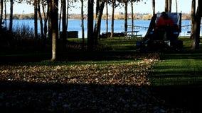 Bemidji, MN - 23 ottobre 2018: L'uomo taglia l'erba e raccoglie il permesso di autunno video d archivio