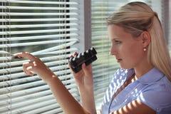 Bemoeizieke vrouw die door sommige zonneblinden tuurt Royalty-vrije Stock Foto's