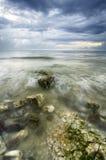 Bemoste rotsen langs de kustlijn met dramatische donkere wolken Stock Foto