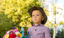 Bemused little boy with flowers Stock Photo