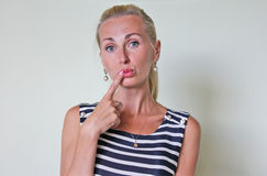 A bemused woman with a finger next to her mouth. Beautiful young blonde girl in the sea striped blue dress and pearl earrings stumped, thoughtful, confused, does Stock Images