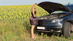 Bemused woman looking at car engine Stock Photography