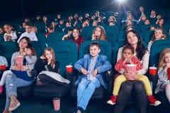 Bemuttern Sie aufpassenden Film mit kleinen Kindern auf erster Kinoreihe lizenzfreie stockbilder