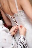 Bemuttern Sie binden Hochzeitskleid ihrer Tochter im Weiß Stockfotos