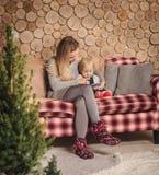 Bemuttern Sie das Ablesen eines Buches mit Babytochter vor Weihnachten lizenzfreies stockbild