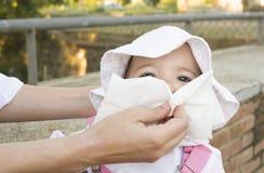 Bemuttern Sie das Abwischen der Nase ihrer Babytochter Lizenzfreies Stockfoto