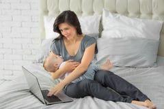 Bemuttern Sie das Arbeiten an Laptop mit einem kleinen Kind stockfotos