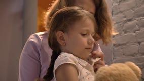 Bemuttern Sie das Einfassungshaar ihrer kleinen Tochter und des Küssens sie und in lebendem modernem Raum zuhause sitzen, Familie stock video footage