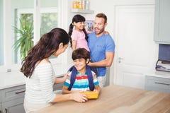 Bemuttern Sie das Geben dem Sohn mit Vater tragendem daughte der Brotdose Stockfoto