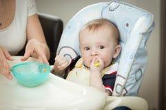 Bemuttern Sie das Geben ihrem Babysohn des Tellers, der im Highchair sitzt Stockfoto