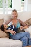 Bemuttern Sie das Geben ihrem Sohn einer Flasche Milch stockfotos