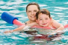 Bemuttern Sie das Geben Sohn einer Schwimmenlektion im Pool Stockfoto