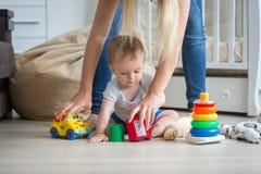 Bemuttern Sie das Geben von Spielwaren zu ihren 10 Monate alten Baby, die auf floo spielen Lizenzfreie Stockbilder
