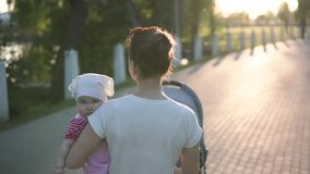 Bemuttern Sie das Gehen mit Baby in den Händen auf der Parkstraße, slowmotion Schuss, Sonne ist glänzend stock footage