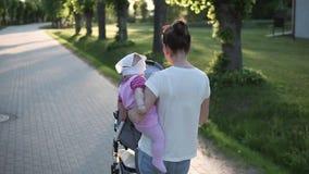 Bemuttern Sie das Gehen mit Baby in den Händen, Sonne ist glänzend, trägt einen Spaziergänger stock video