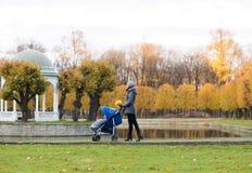 Bemuttern Sie das Gehen mit einem Baby Pram im Park Stockbild