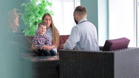 Bemuttern Sie das Halten auf ihrem kleinen Sohn der Knie, der im Stuhl sitzt, der mit Doktor spricht stock video footage