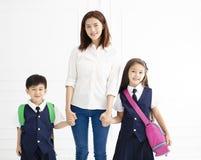 Bemuttern Sie das Halten der Hand der Kinder bereit gehen zur Schule Stockfotografie