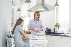 Bemuttern Sie das Halten der Kaffeetasse beim Betrachten der Tochter, die in der Küche studiert Stockbild