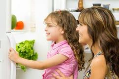 Bemuttern Sie das Halten der Tochter in der modernen Küchenöffnungs-Kühlschranktür, die nach innen glücklich schaut Lizenzfreies Stockfoto