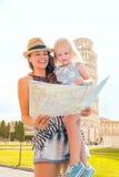 Bemuttern Sie das Halten der Tochter, die Karte in Pisa im Sommer betrachtet Lizenzfreie Stockbilder