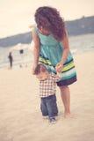 Bemuttern Sie das Halten des Babys für den ersten Schritt auf dem Strand Lizenzfreie Stockfotos