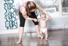 Bemuttern Sie das Halten eines Babys unter seinen Armen im Wohnzimmer lizenzfreies stockbild