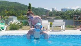 Bemuttern Sie das Halten ihres Babys und er Spaß im Swimmingpool habend stock footage