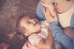 Bemuttern Sie das Halten ihres kleinen Mädchens in den Armen und das Überziehen mit ihr stockbilder