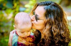 Bemuttern Sie das Halten und das Küssen eines Babys in ihren Händen im Park Stockfotos