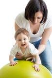 Bemuttern Sie das Handeln von Gymnastik mit Baby auf Eignungsball Stockbilder