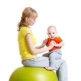 Bemuttern Sie das Handeln von Gymnastik mit Baby auf Eignungsball Lizenzfreie Stockfotos