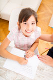 Bemuttern Sie das Helfen ihrer Tochter mit der Heimarbeit Lizenzfreie Stockfotografie