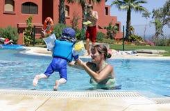 Bemuttern Sie das Helfen ihres jungen Sohns, in ein sonniges swimmin zu schwimmen und zu springen stockfotografie