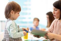Bemuttern Sie das Helfen ihres Kindes, farbiges Papier zu schneiden stockfotografie