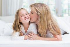 Bemuttern Sie das Küssen ihrer Tochter auf der Backe im Bett stockfotografie