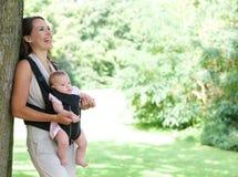 Bemuttern Sie das Lächeln im Park mit Baby im Riemen lizenzfreie stockfotografie