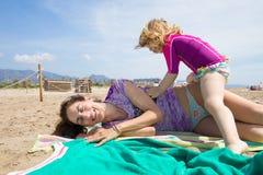 Bemuttern Sie das Lachen mit dem kleinen Kind, das auf Tüchern am Strand sitzt Lizenzfreie Stockfotos