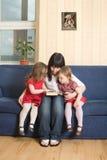 Bemuttern Sie das Lesen eines Buches mit ihren kleinen Töchtern Stockbilder
