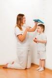 Bemuttern Sie das Messen der Höhe ihres Sohns an der Wand Stockbilder