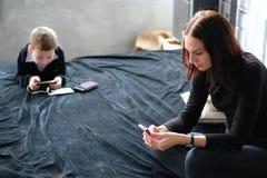 Bemuttern Sie das Plaudern und ihren Sohn Spiele am intelligenten Telefon spielend Co stockbild