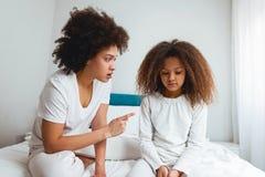 Bemuttern Sie das Schelten ihrer Tochter und im Schlafzimmer sitzen Lizenzfreie Stockfotos