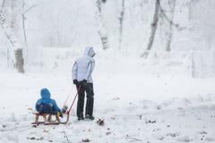 Bemuttern Sie das Schleppen des Schneeschlittens mit ihrem Kind hinten Lizenzfreies Stockfoto
