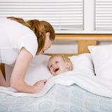 Bemuttern Sie das Setzen des gesprächigen Sohns, um an der Schlafenszeit zu Bett zu gehen Lizenzfreie Stockbilder